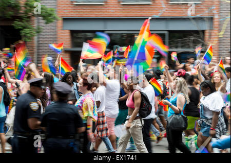 NEW YORK CITY, USA - JUNE 28, 2015: Celebrants at the annual gay pride parade wave rainbow flags as they pass police. - Stock Photo