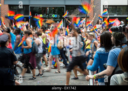NEW YORK CITY, USA - JUNE 28, 2015: Celebrants at the annual gay pride parade wave rainbow flags as they pass spectators. - Stock Photo