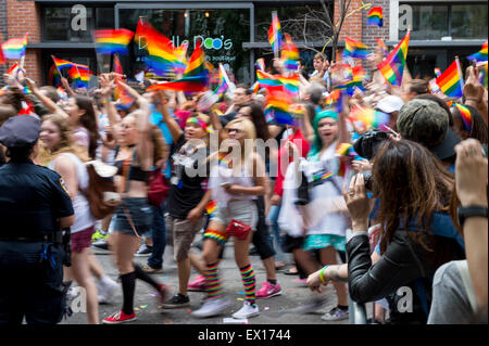 NEW YORK CITY, USA - JUNE 28, 2015: Celebrants at the annual gay pride parade wave rainbow flags passing cheering - Stock Photo