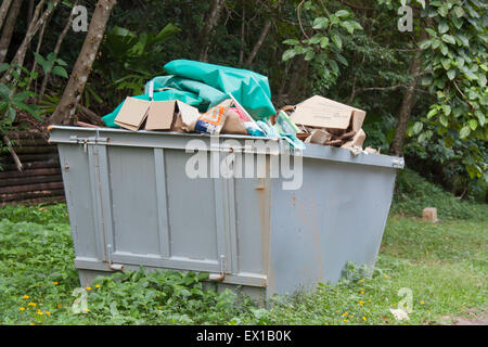 a tip skip bin filled with rubbish - Stock Photo