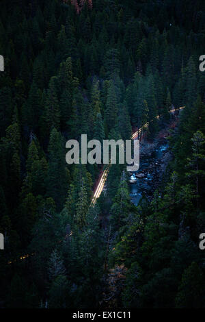 Car headlights at dawn along the Yosemite Valley floor. High shot from above Tunnel View - Stock Photo