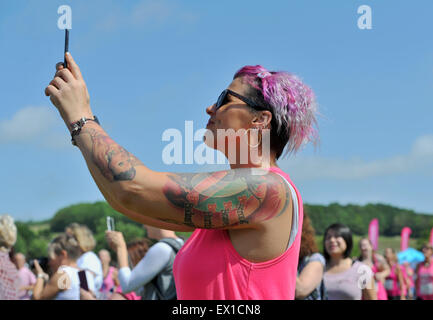 Brighton UK Saturday 4th July 2015 - A young woman with tattoos takes a selfie photograph at the Cancer Research - Stock Photo