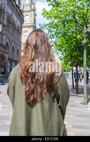 Beautiful, young girl with long brown hair standing with her back to the camera in the streets of big city. - Stock Photo