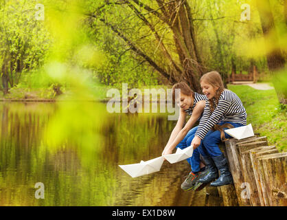 Boy and girl in striped shirts play paper boats - Stock Photo