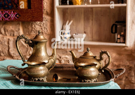 Dinner set of dishes for coffee and tea from the old bronze bell on the tray with the call for workers - Stock Photo