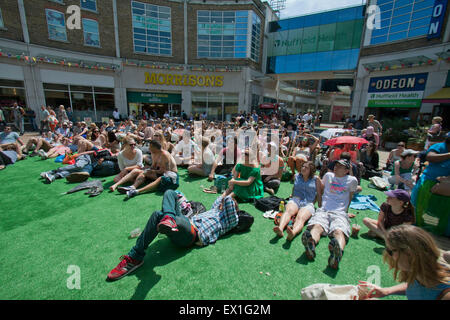Wimbledon, London, UK. 04th July, 2015. People watch a live tennis match between Roger Federer and Sam Groth on - Stock Photo