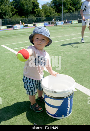 A one year old boy offers a red tennis ball - see description - as kids line up to hit with British tennis stars in Wimbledon Park halfway through The Wimbledon tennis Championships Stock Photo