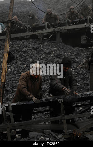 Miners prepare coal for transport at a coal mine site in Changzhi, Shanxi province February 7, 2010. VCP - Stock Photo