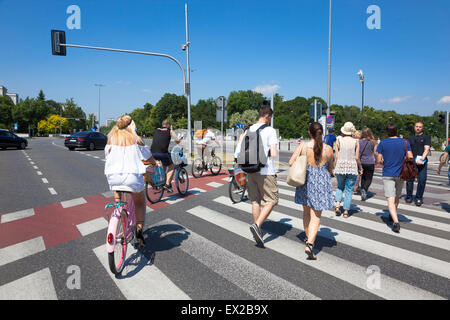 Pedestrians and cyclists crossing the road in Warsaw, Poland - Stock Photo