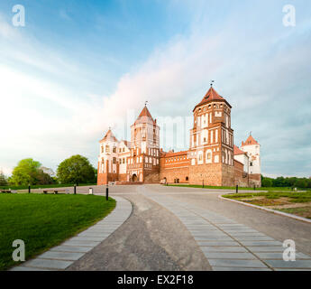 Green trees and gras and blue sky at sunny day. Stone road to beautiful Mir castle in Belarus. Medieval fort became - Stock Photo