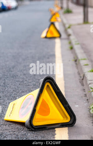 Traffic cones lie on a road after being kicked over by children - Stock Photo
