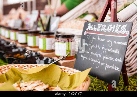Sign at a market stall advising people with allergies to check with staff before sampling or purchasing. - Stock Photo