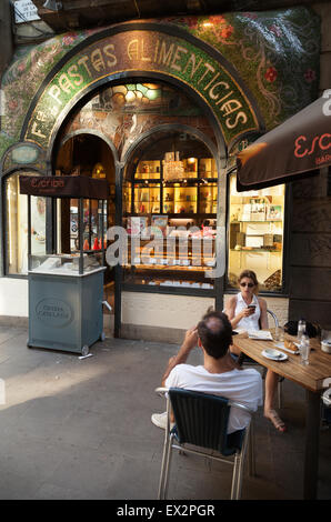 People eating outside at the Escriba pastry shop cafe on Las Ramblas, Barcelona, Spain Europe - Stock Photo