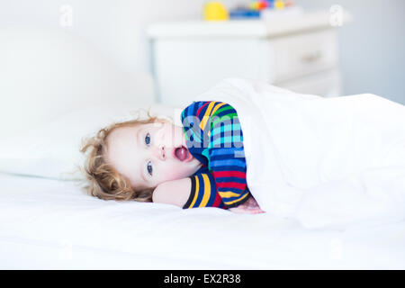 Funny yawning toddler girl waking up in the morning in a sunny white bedroom - Stock Photo