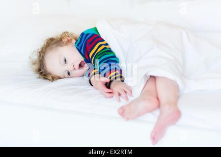 Funny yawning toddler girl taking a nap in a white bed - Stock Photo