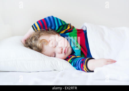 Funny sleeping toddler girl in a white bed - Stock Photo