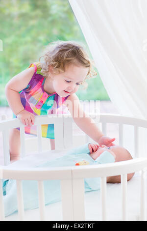 Adorable little toddler girl with curly hair playing with her newborn baby brother in a white round bed next to - Stock Photo