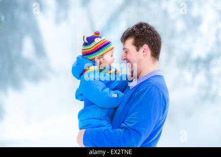 Young father playing with his funny baby in a snowy park - Stock Photo