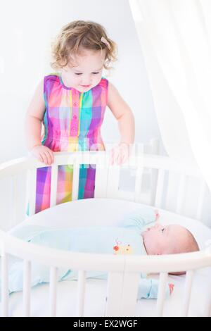 Cute newborn baby boy looking at his toddler sister standing at his white round crib on a sunny morning - Stock Photo