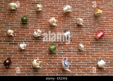 All kinds of teapots hanging on a wall as a decoration in the city of Oudewater, Utrecht, The Netherlands. - Stock Photo