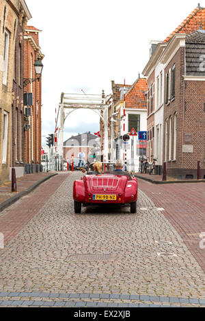 Driving with the hardtop down across cobblestone streets through the charming, historic city of Oudewater, Utrecht, - Stock Photo