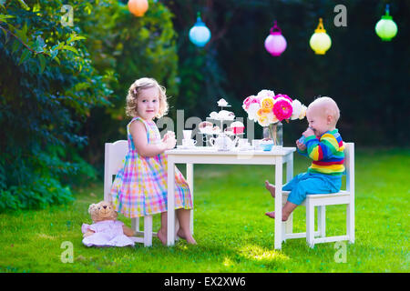 Garden birthday party for children. Kids outdoor celebration. Little boy and girl drinking tea and eating cake in - Stock Photo