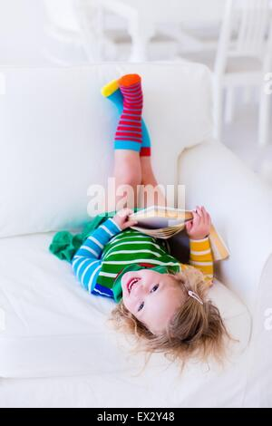 Little girl reading a book relaxing on a white couch. Kids read books at home or preschool. Children learning and - Stock Photo