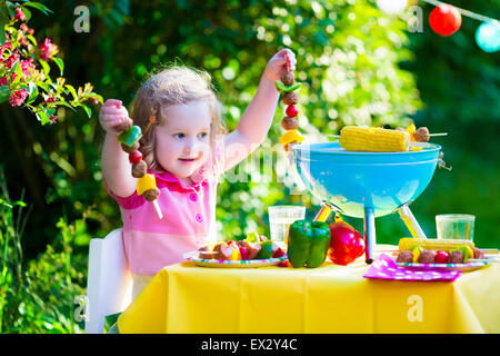 Children grilling meat. Family camping and enjoying BBQ. Little girl at barbecue preparing steaks, kebab and corn. - Stock Photo