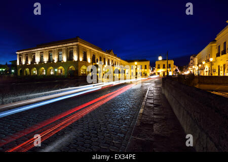 Indigo sky and car lights over Plaza Espana and Puente Nuevo bridge at dusk in Ronda Spain - Stock Photo