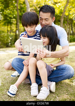 father and children using ipad in park - Stock Photo