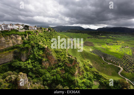 Dappled sunshine on green fields in spring at El Tajo gorge at the mountain city of Ronda Spain at the Guadalevin - Stock Photo