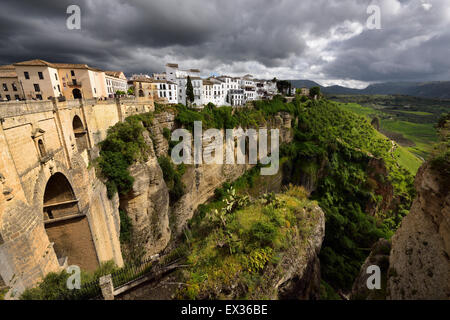 Dark clouds and dappled sunshine on cliff and new bridge of mountain city Ronda Spain at the El Tajo Gorge gorge - Stock Photo