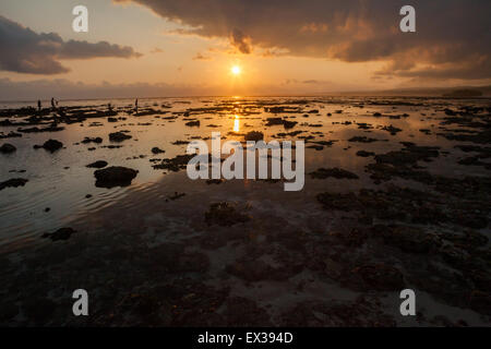 Panoramic view of a rocky beach during sunset on tropical island. - Stock Photo