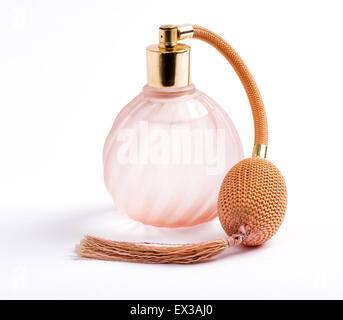 Classic perfume bottle with an atomizer pump for spraying the scent with attached long tassel in ridged swirling - Stock Photo