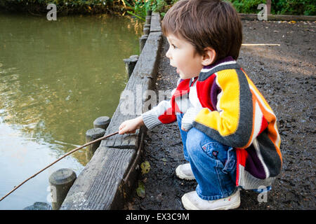 3 to 5 year old Caucasian boy, outdoors. Crouching on river jetty by water's edge, using stick as fishing rod. Side - Stock Photo