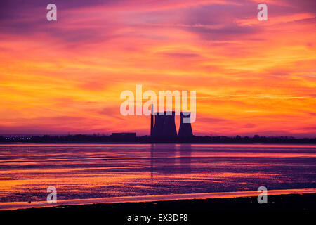Vivid red and yellow sky after sunset over Pegwell Bay in Kent with the three disused cooling towers, (now gone), - Stock Photo