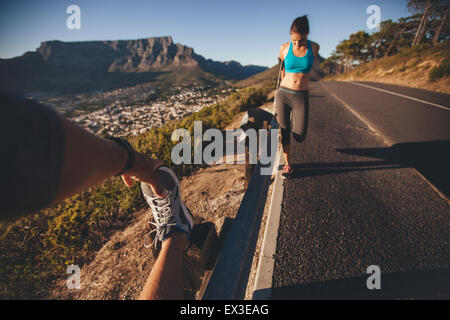 POV shot of man stretching his leg with woman exercising by a road guardrail. Young people relaxing their muscles - Stock Photo