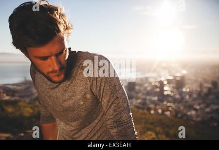 Close up shot of young man resting after running workout. Runner outdoors with bright sunlight. Athlete relaxing - Stock Photo