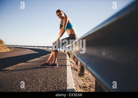 Tired young woman relaxing after a outdoor training session. Runner resting on road guardrail after morning run. - Stock Photo