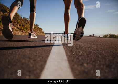 Cropped shot of runners running on the road. Rear view close-up image of man and woman jogging outdoors. Focus on - Stock Photo