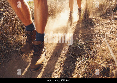 Low section shot of two young people walking on dirt trail, focus on men's hiking boots. Couple of hikers on country - Stock Photo