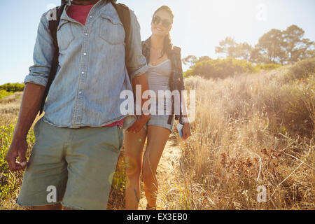 Image of young woman hiking in mountains with her boyfriend in front. Couple walking downhill on summer vacation. - Stock Photo