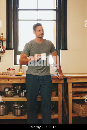 Portrait of man standing in kitchen holding a cup of coffee looking away in thought. Relaxed young man having coffee - Stock Photo