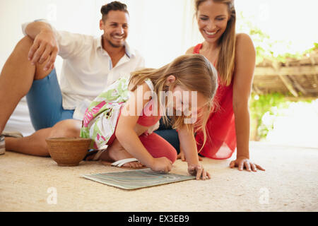 Shot of little girl drawing picture with her parents sitting behind her in living room. Family sitting on floor - Stock Photo