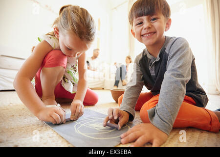 Indoor shot of happy little children drawing and coloring sitting on floor with parents in background at home - Stock Photo