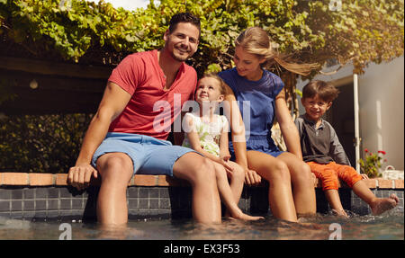 Outdoor shot of beautiful young family sitting next to swimming pool with their feet in water. Young couple with - Stock Photo