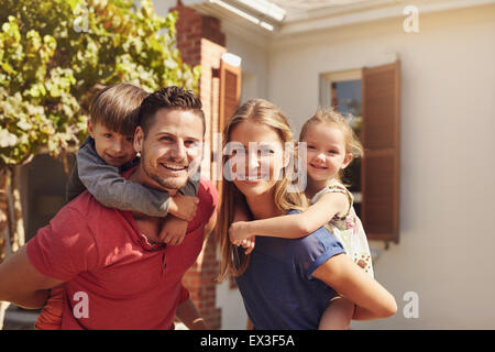 Portrait of a happy couple carrying their children on their backs. Parents giving their children piggyback rides - Stock Photo
