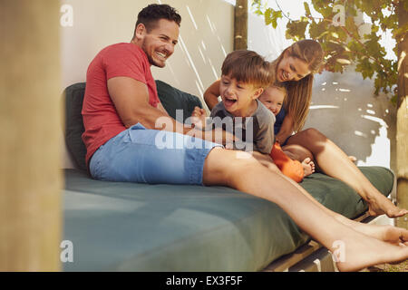 Happy family sitting together in the backyard, having fun. Father and mother playing with their kids while sitting - Stock Photo