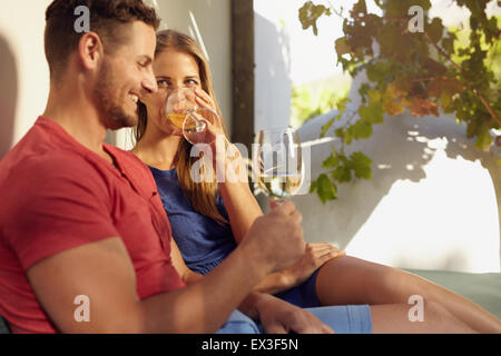 Portrait of young couple relaxing outdoors drinking wine together. - Stock Photo