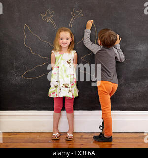 Full length portrait of cute little girl standing and little boy drawing angel wings around her on blackboard. - Stock Photo